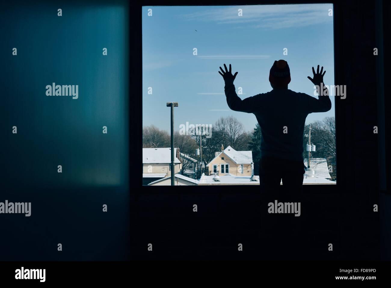 Vista posteriore di Silhouette uomo in piedi alla finestra Immagini Stock