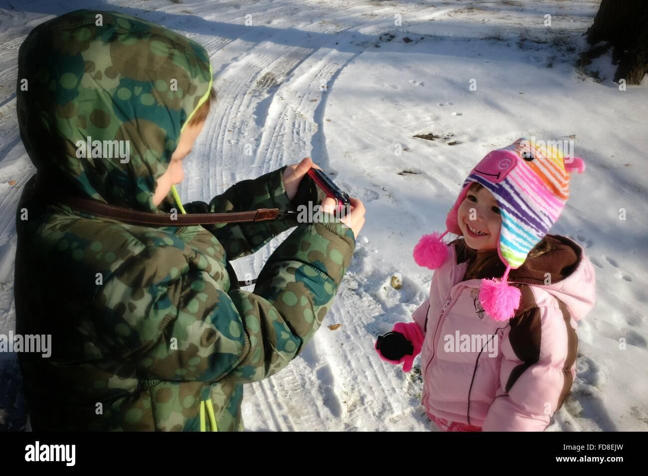 Fratello di fotografare la sorella su strade coperte di neve campo Immagini Stock