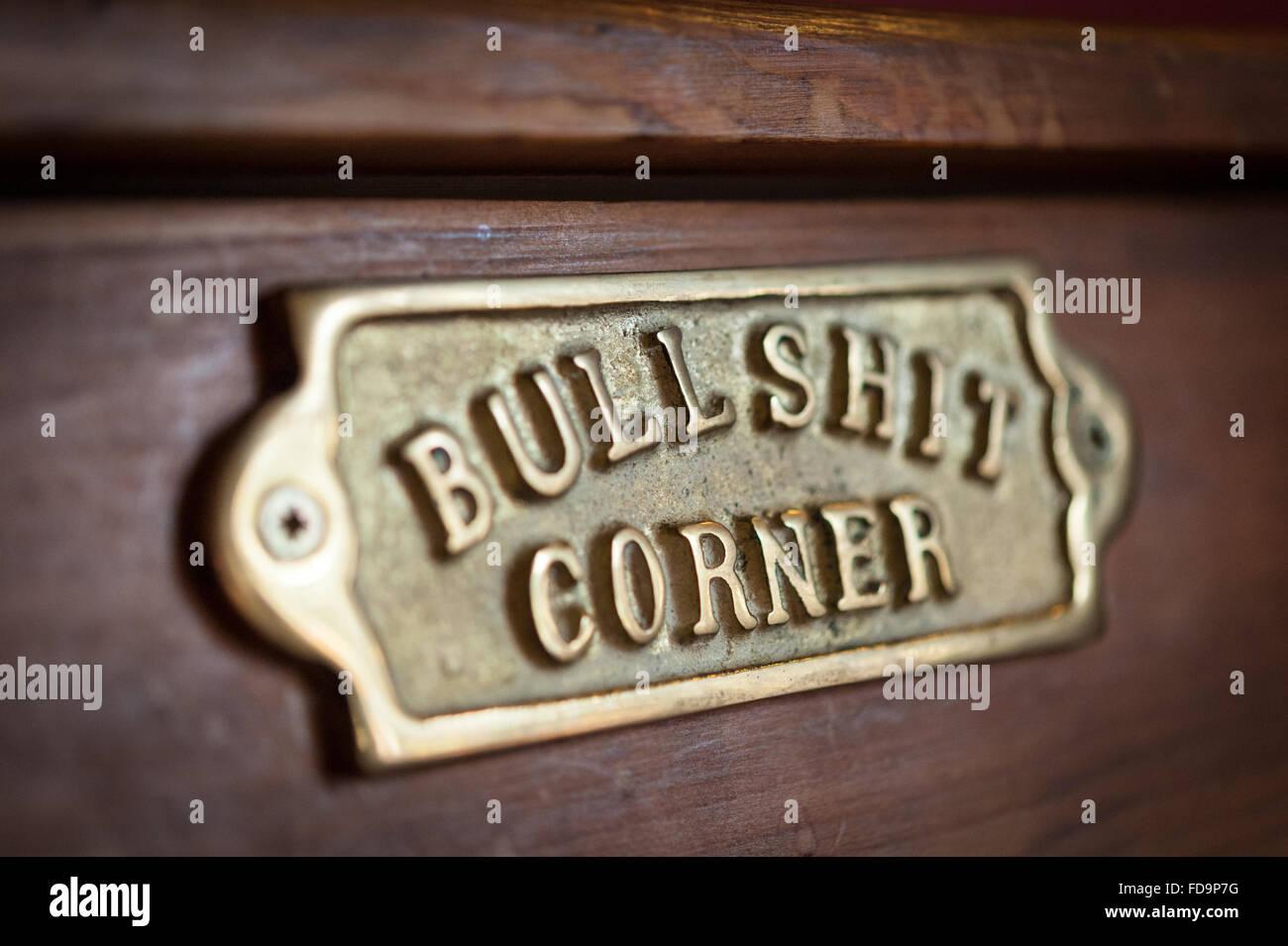 Un divertente targa in ottone firmare in un pub con le parole stronzate angolo su Foto Stock