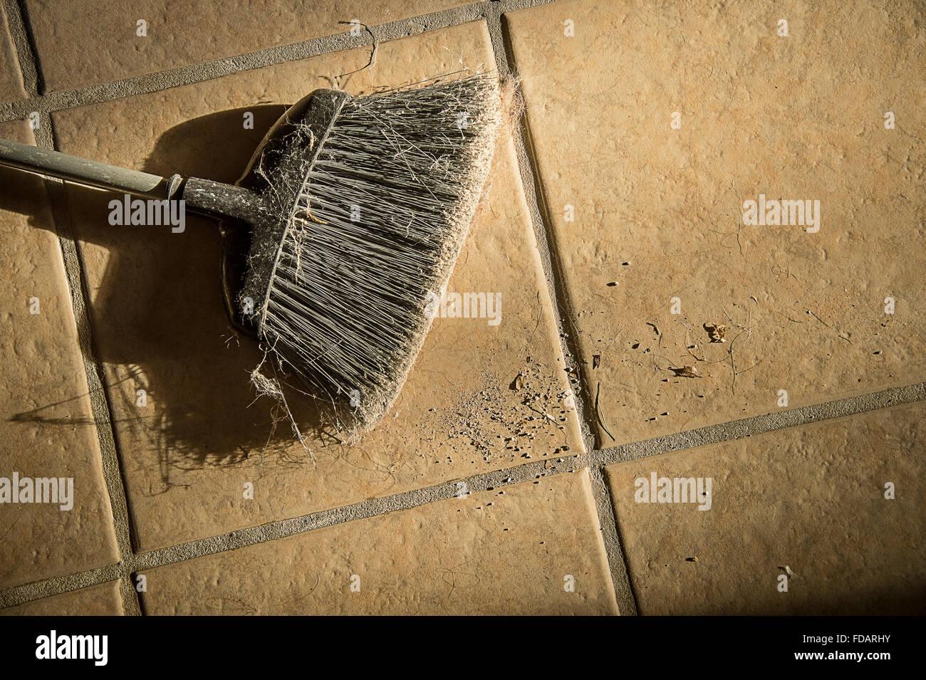 Scopa vecchia sul pavimento di piastrelle con il mucchio di sporcizia Immagini Stock