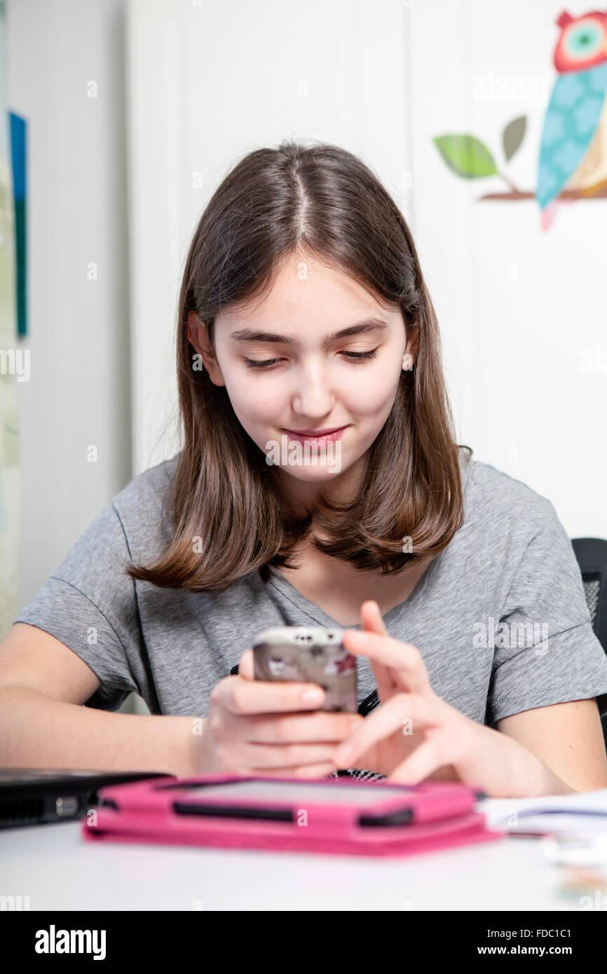 La teenager con il cellulare a casa Immagini Stock