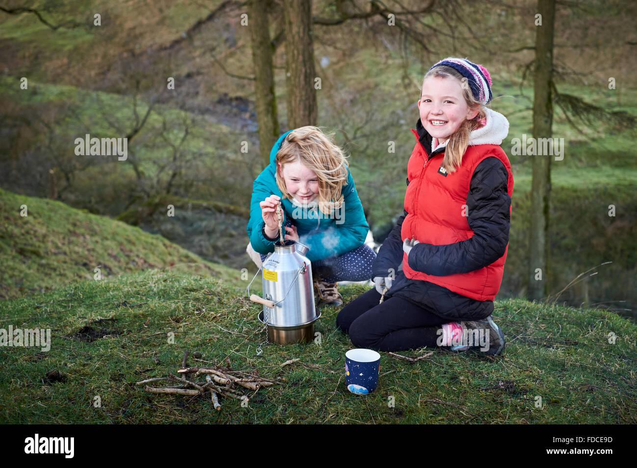 Due ragazze utilizzando un bollitore Kelly Stufa per cucinare all'aperto sorridente e aggiunta di legna per Immagini Stock