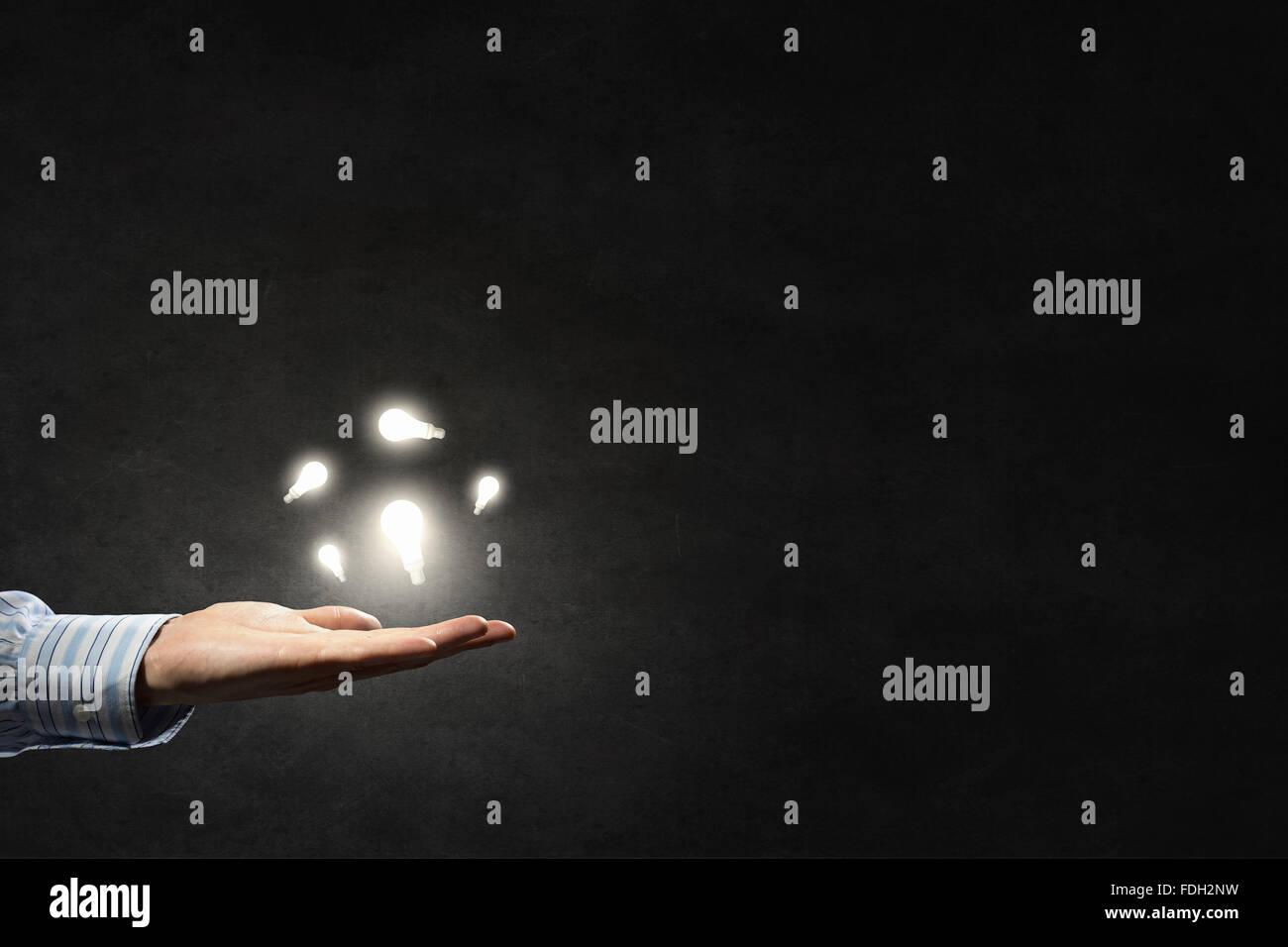 Imprenditore illuminato con luce di vetro lampadina in mano Immagini Stock