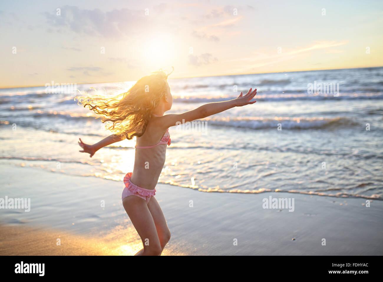 https://c8.alamy.com/compit/fdhyac/felice-bambina-con-ricci-capelli-lunghi-dancing-in-un-costume-da-bagno-durante-il-tramonto-fdhyac.jpg
