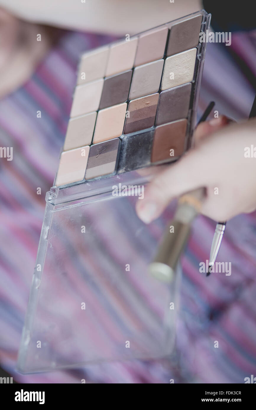 Mano azienda ombretto pallet e make-up pennelli Foto Stock