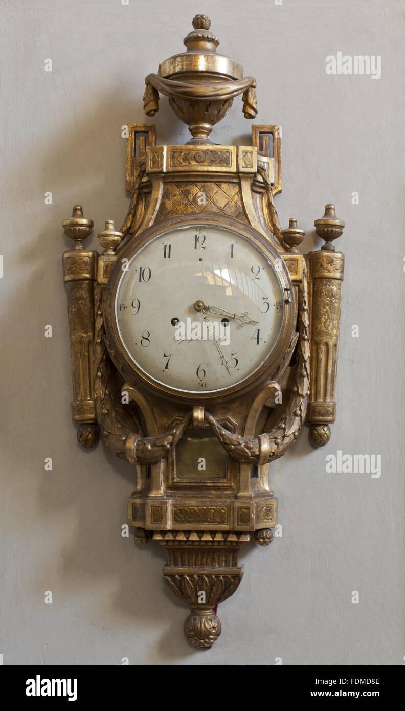 Caso dorato orologio del cartello sul primo piano della scala di pietra a Clandon Park, Surrey. Il clock ha un vaso Immagini Stock