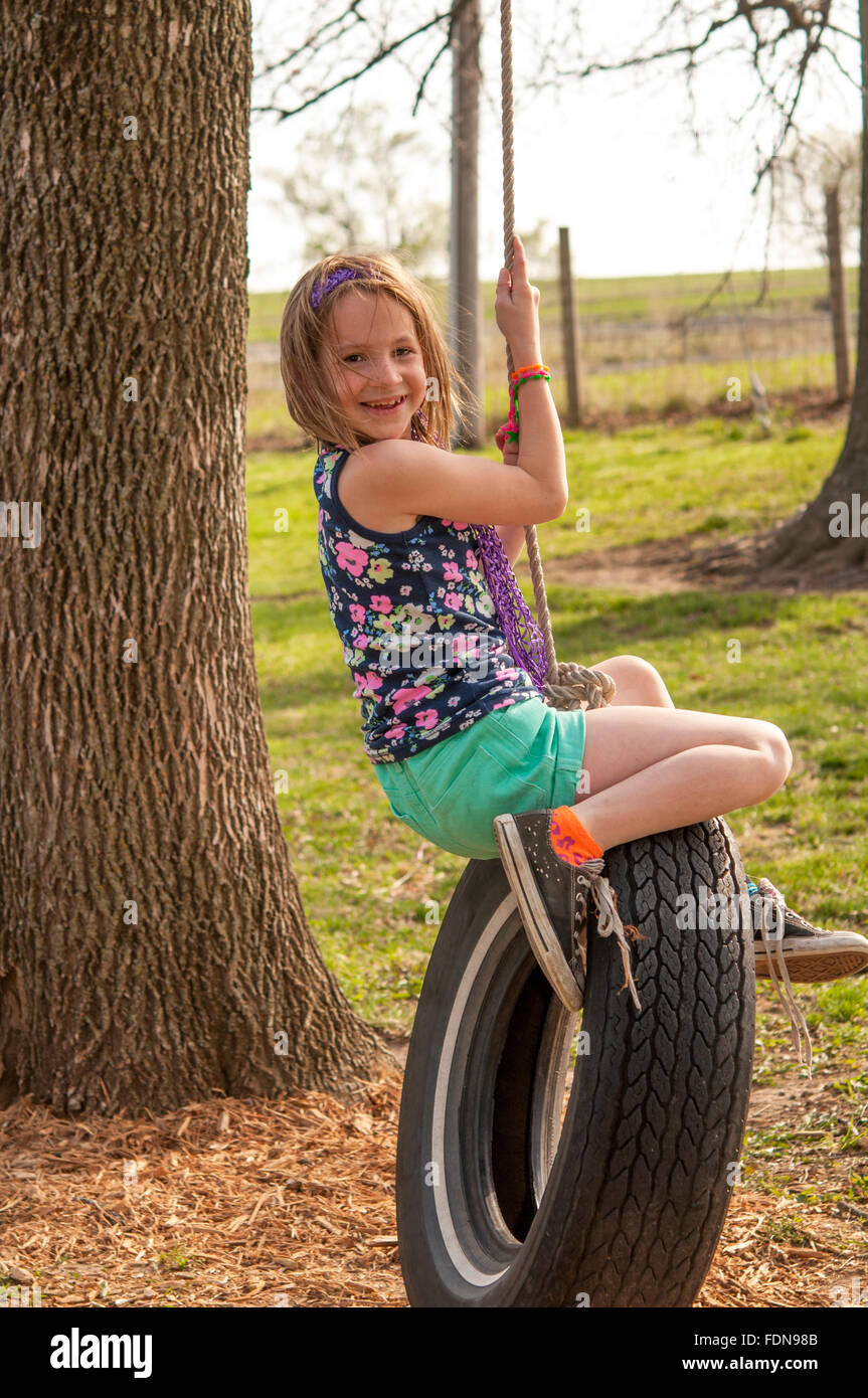 Sorridente ragazza Preteen sulla rotazione dei pneumatici Immagini Stock
