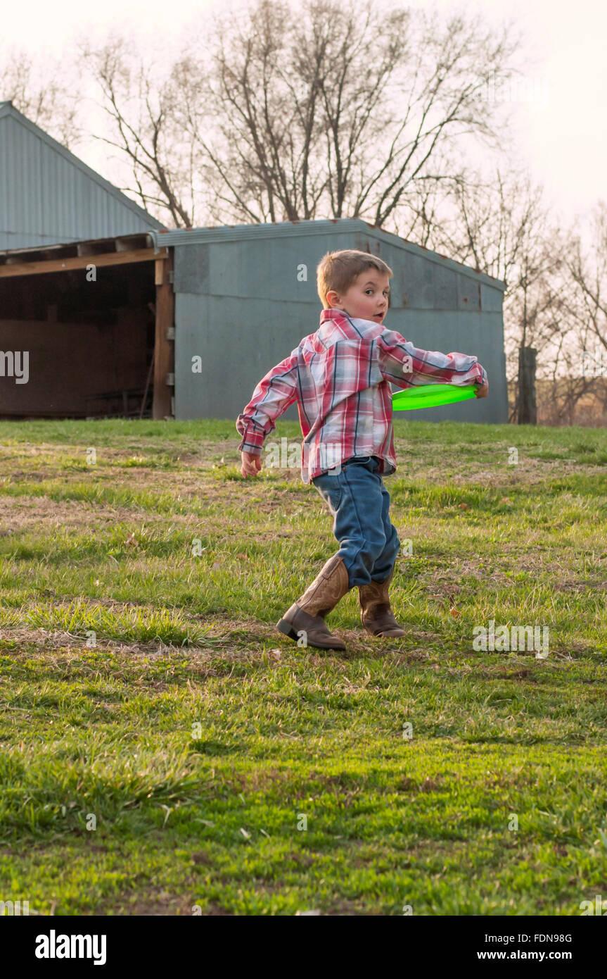 Ragazzo che indossa scarponi gettando frisbee in agriturismo Immagini Stock