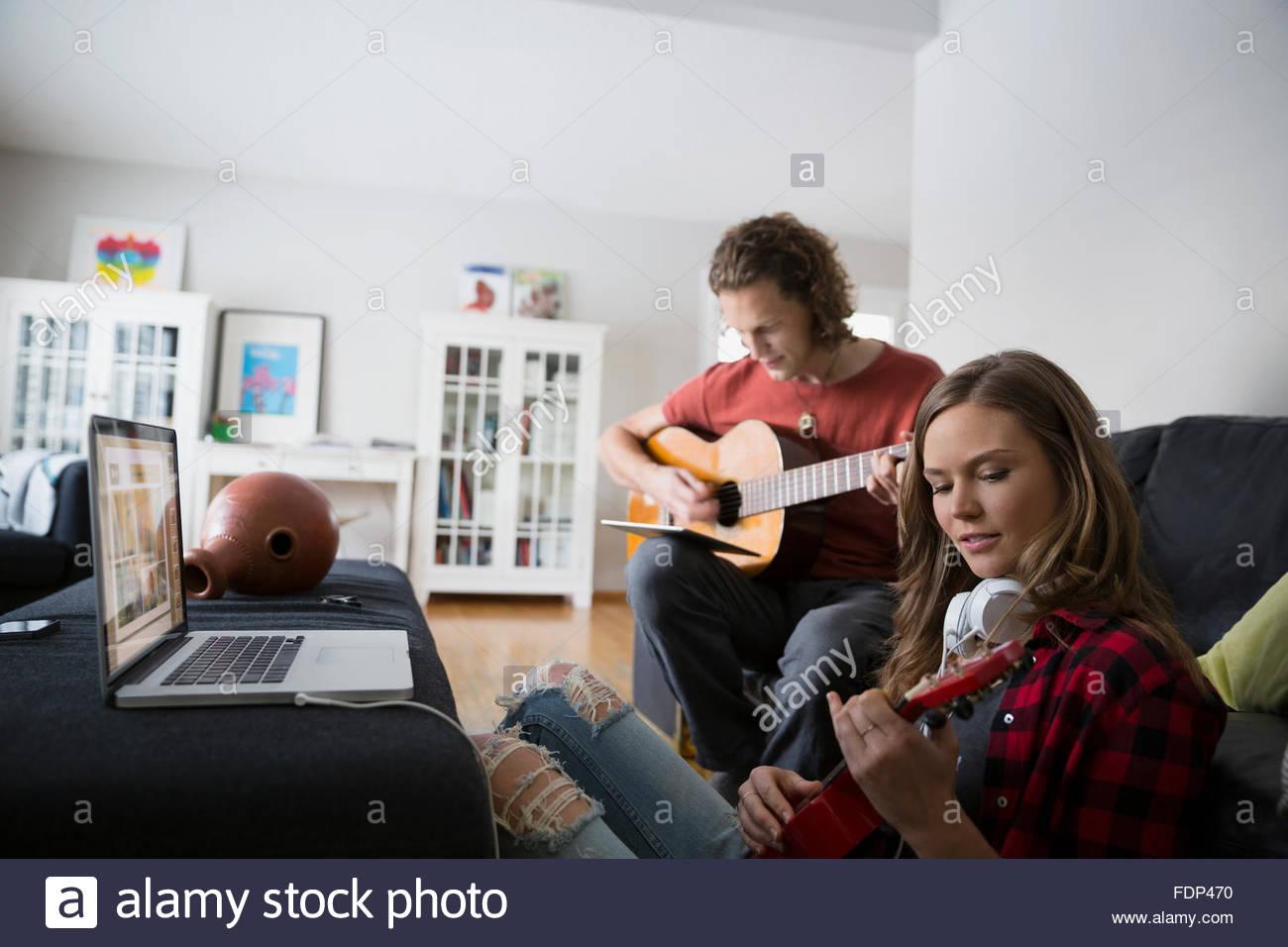 Giovane con laptop a suonare la chitarra e ukulele Immagini Stock