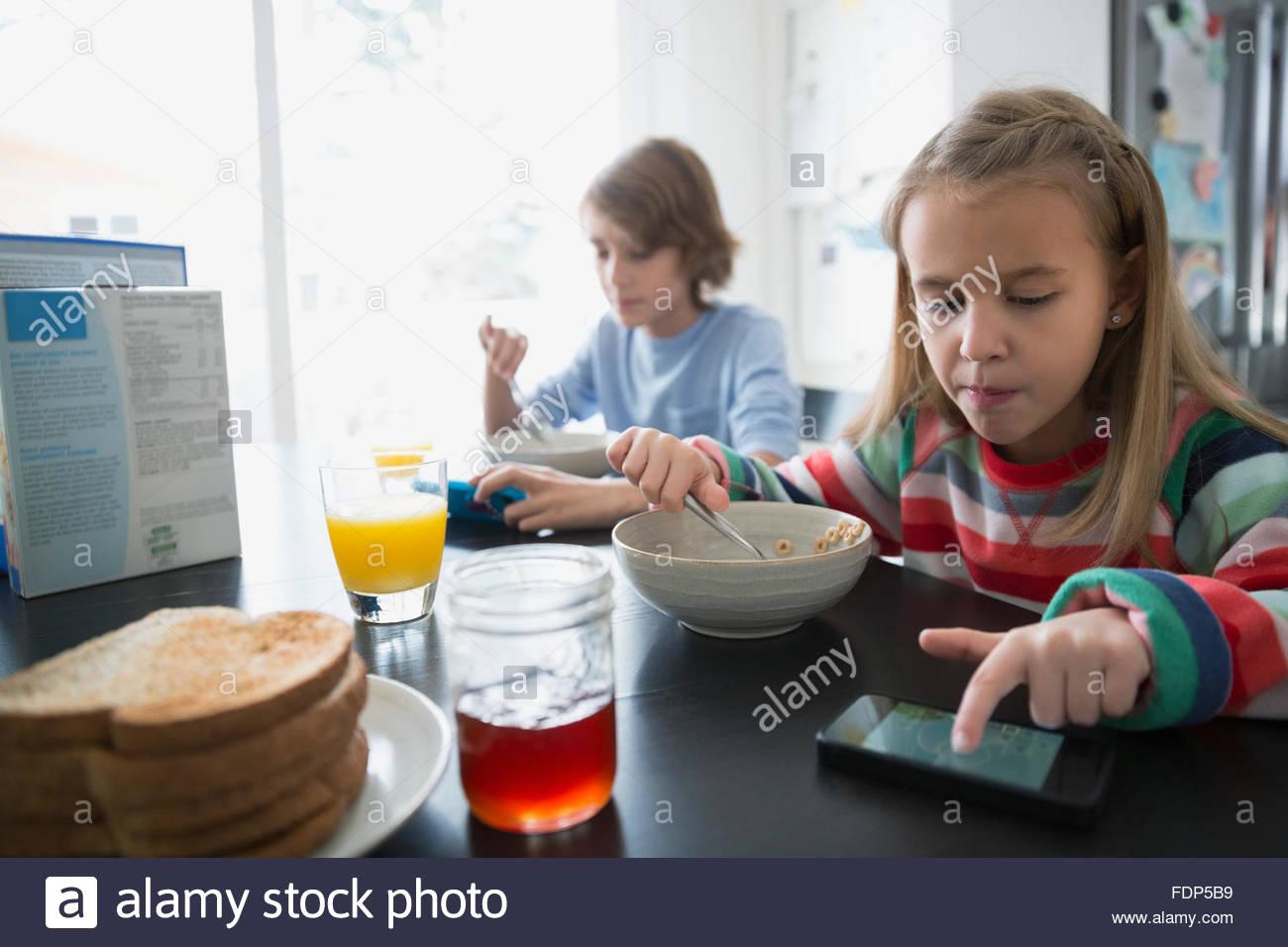 Fratello e Sorella di mangiare la prima colazione i messaggi di testo Immagini Stock