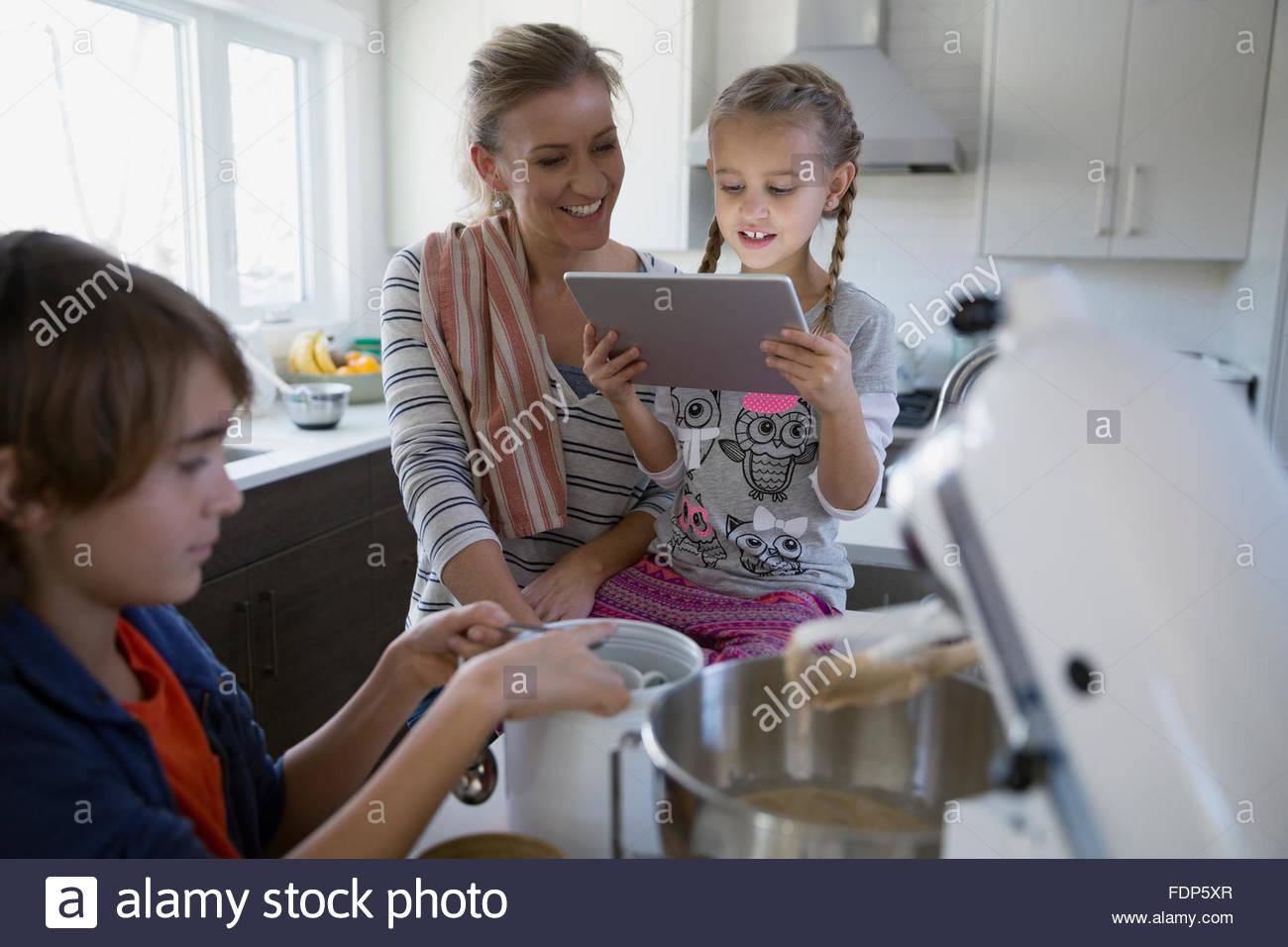 Madre e bambini la cottura con tavoletta digitale cucina Immagini Stock