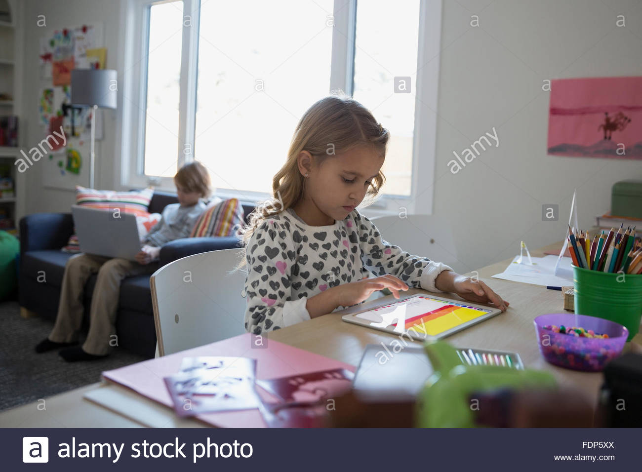 Ragazza con tavoletta digitale alla scrivania Immagini Stock