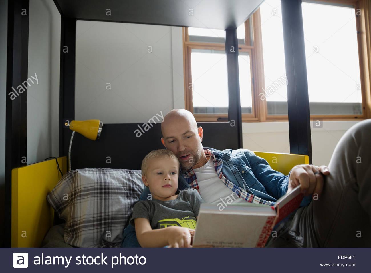 Padre e figlio leggendo un libro sul letto Immagini Stock