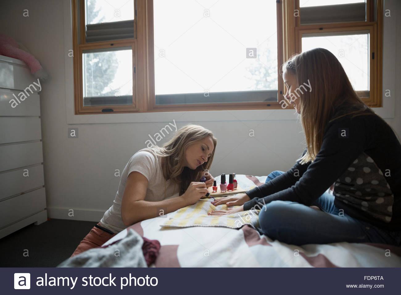 Pittura madre figlie le unghie sul letto Immagini Stock