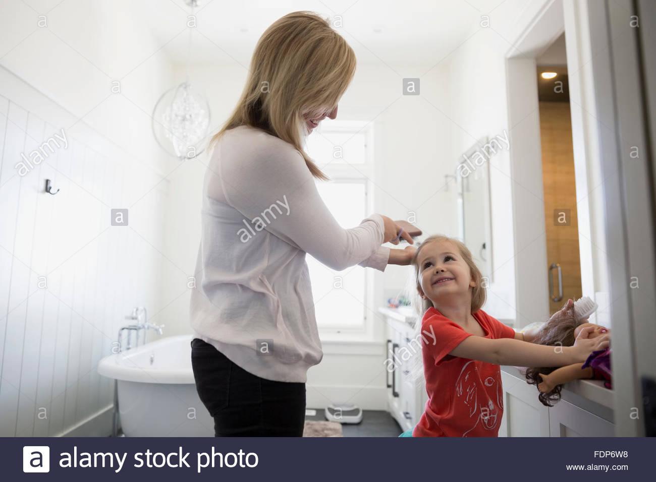 Madre figlie di spazzolatura bagno per capelli Immagini Stock