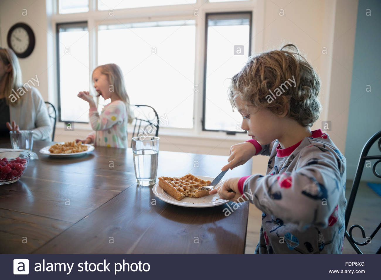 Ragazzo di mangiare waffle al tavolo per la colazione Immagini Stock