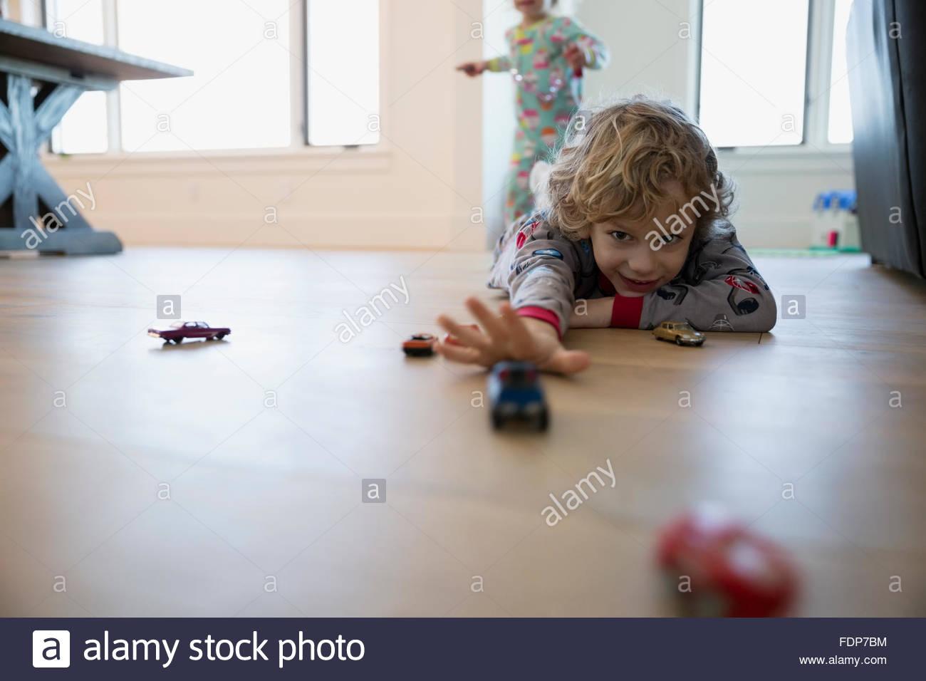 Ragazzo giocando con automobili giocattolo sul pavimento Immagini Stock