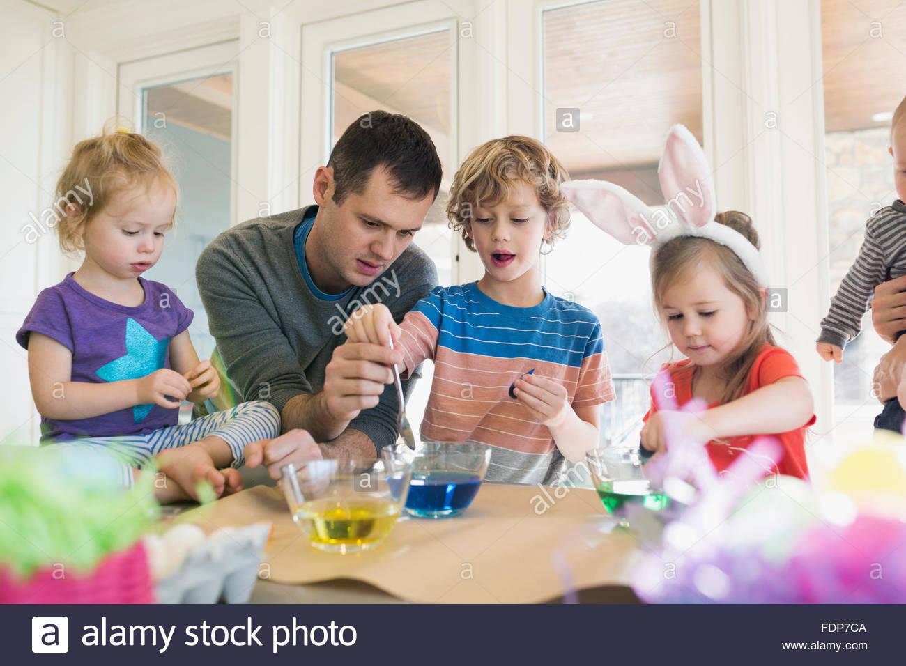 Immersione in famiglia uova di Pasqua nel colorante alimentare Immagini Stock