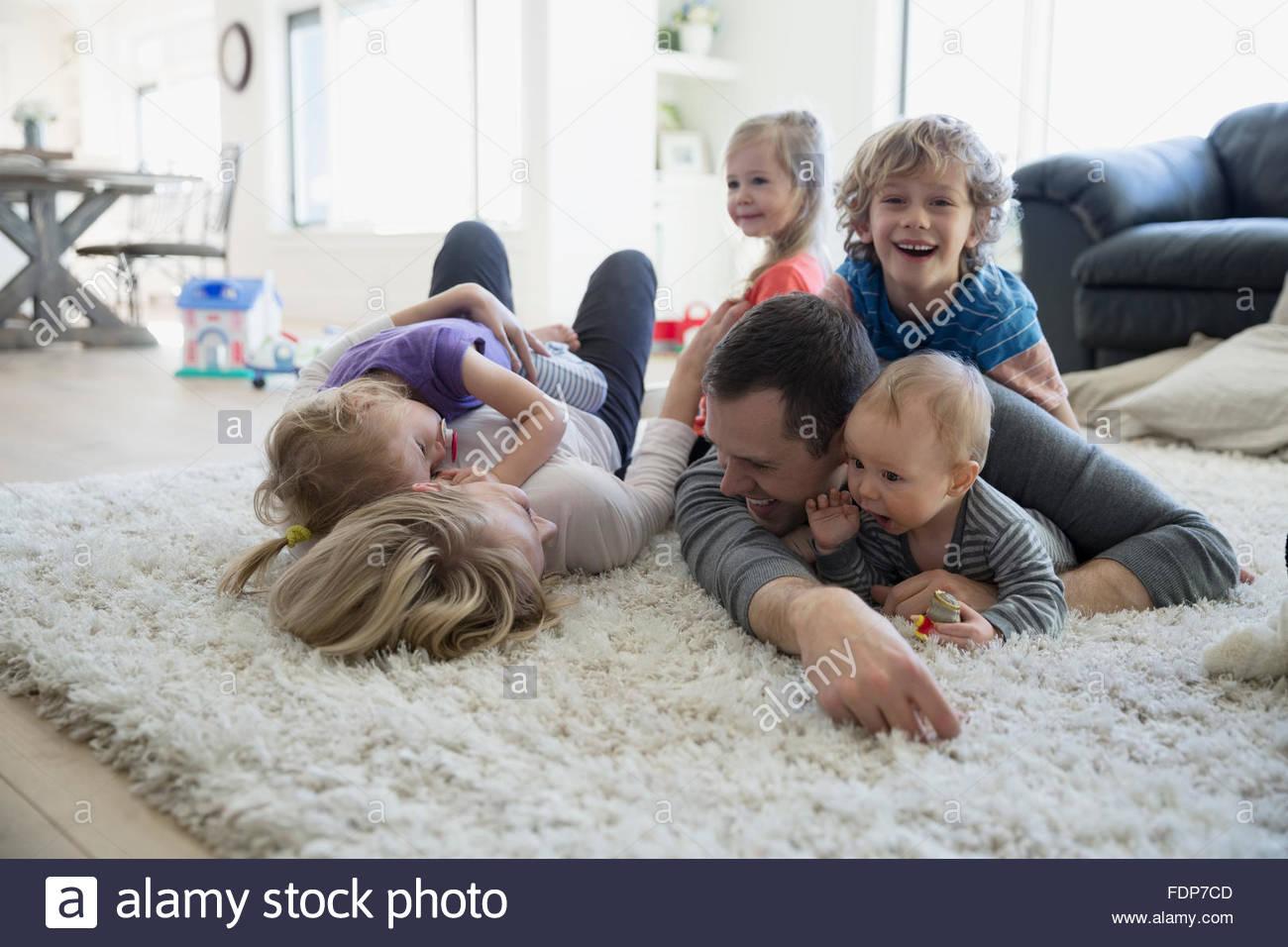 Posa di famiglia e rilassante sulla shag rug Immagini Stock
