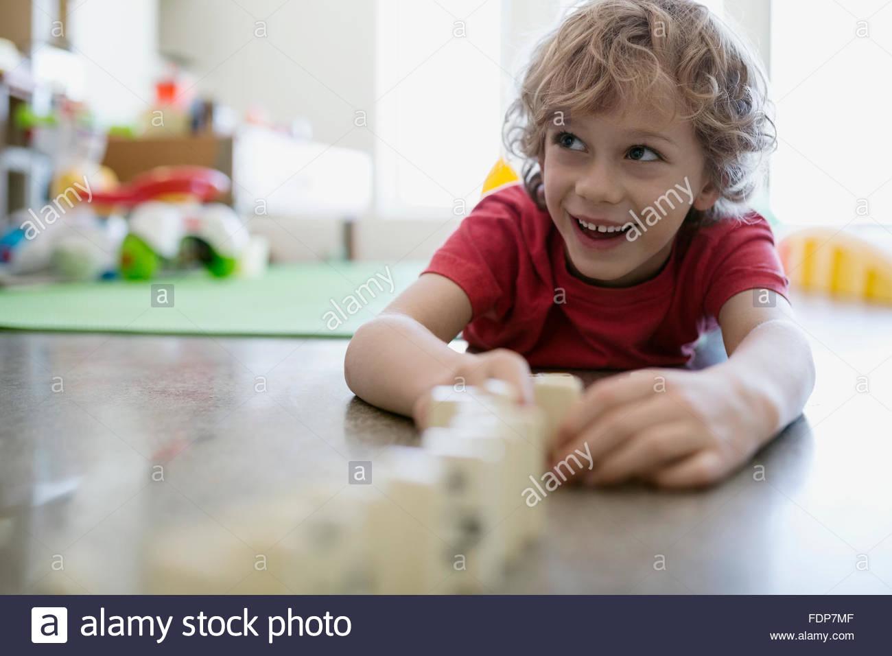 Sorridente ragazzo giocando con effetto domino sul pavimento Immagini Stock