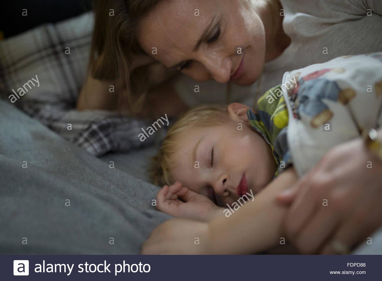 Affettuosa madre guardando figlio che dorme nel letto Immagini Stock