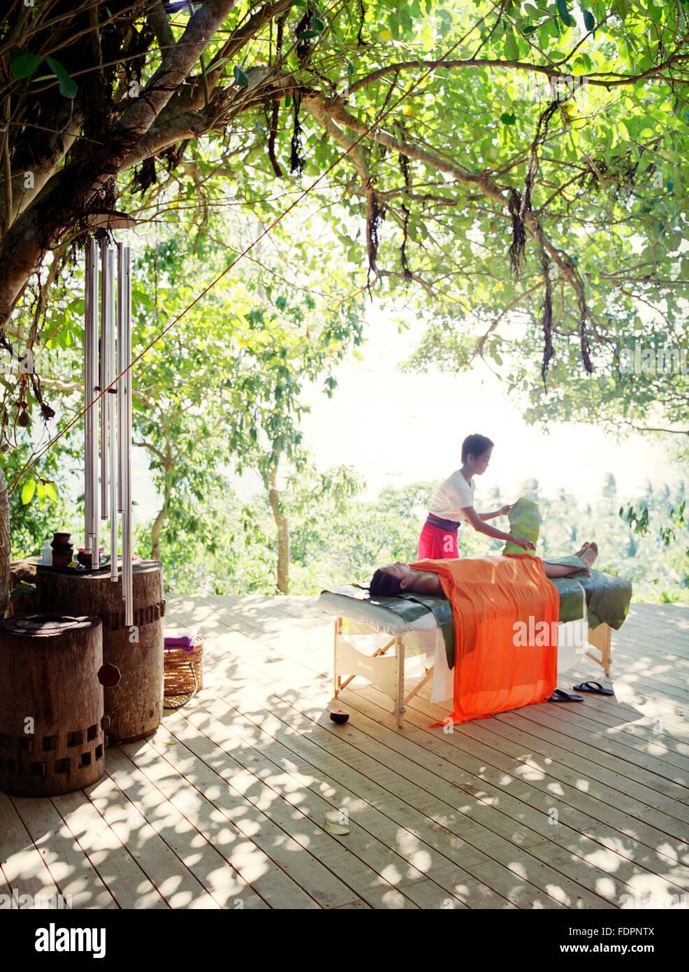 Un terapista applica una Papaya-Pineapple Body polish Wrap per un client. Il Boracay,Filippine Immagini Stock