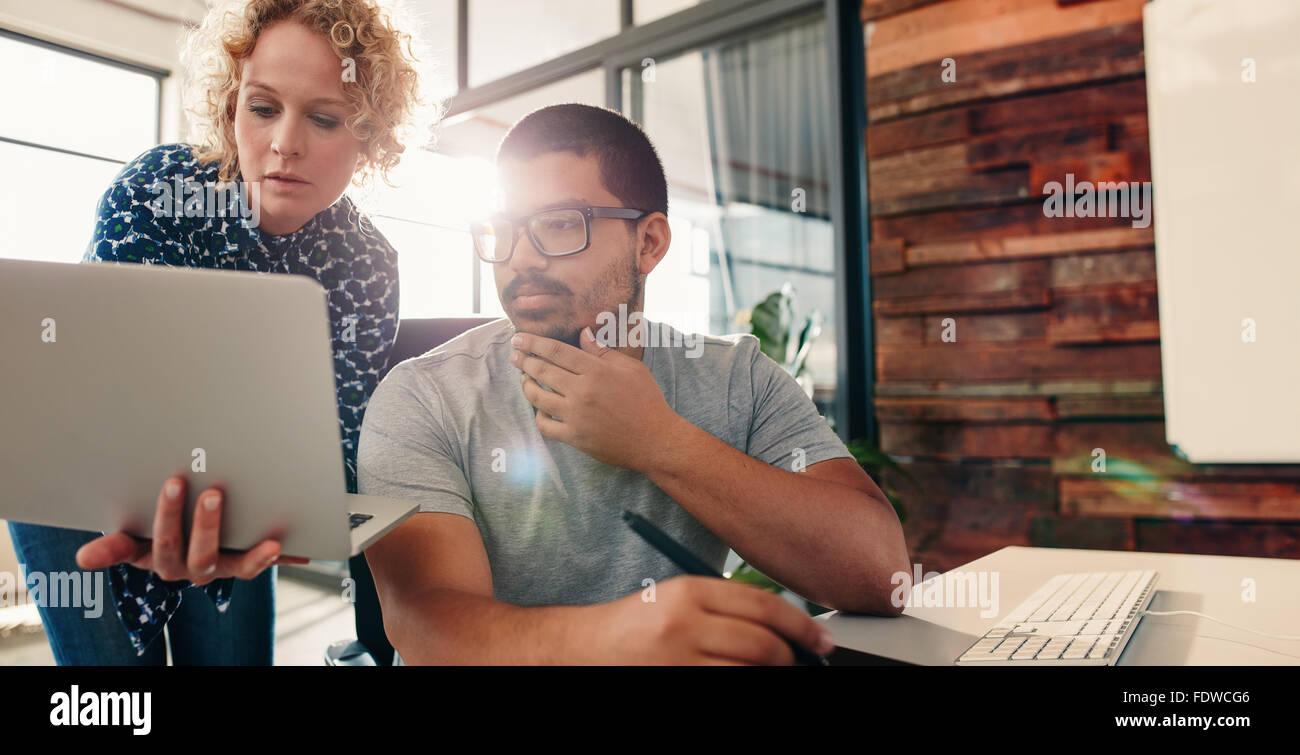 Ritratto di giovane team di graphic designer che lavorano insieme in un nuovo progetto, con la donna che mostra Immagini Stock