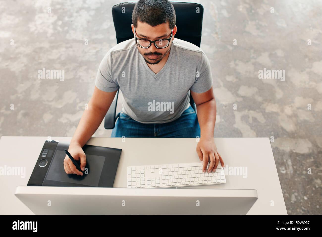 Angolo di alta immagine del giovane uomo usando una penna e tavoletta mentre si lavora sul suo computer. Graphic Foto Stock