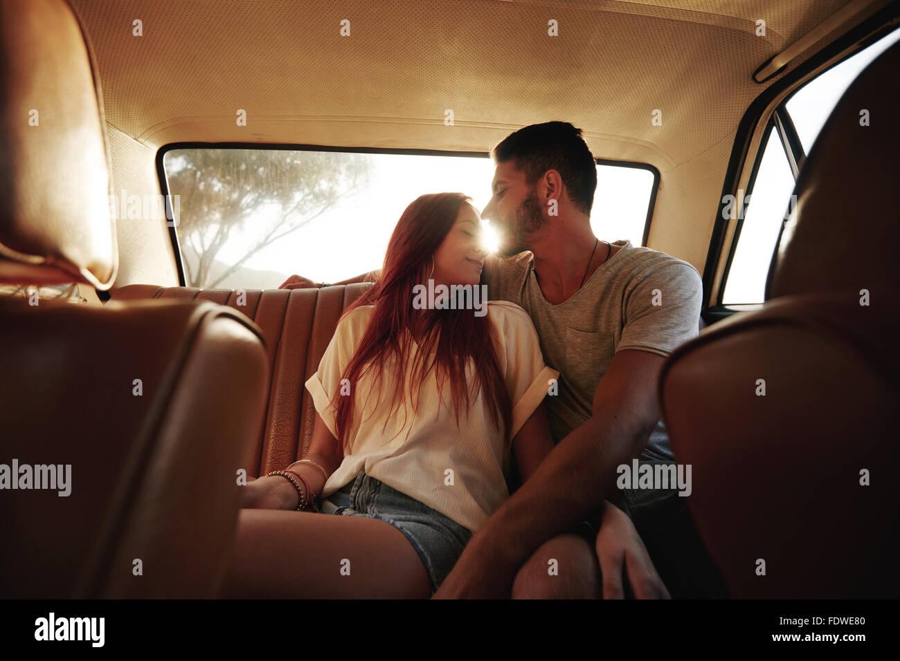 Affettuosa coppia giovane seduto nel sedile posteriore di un auto. Giovane uomo e donna nel sedile posteriore di Immagini Stock