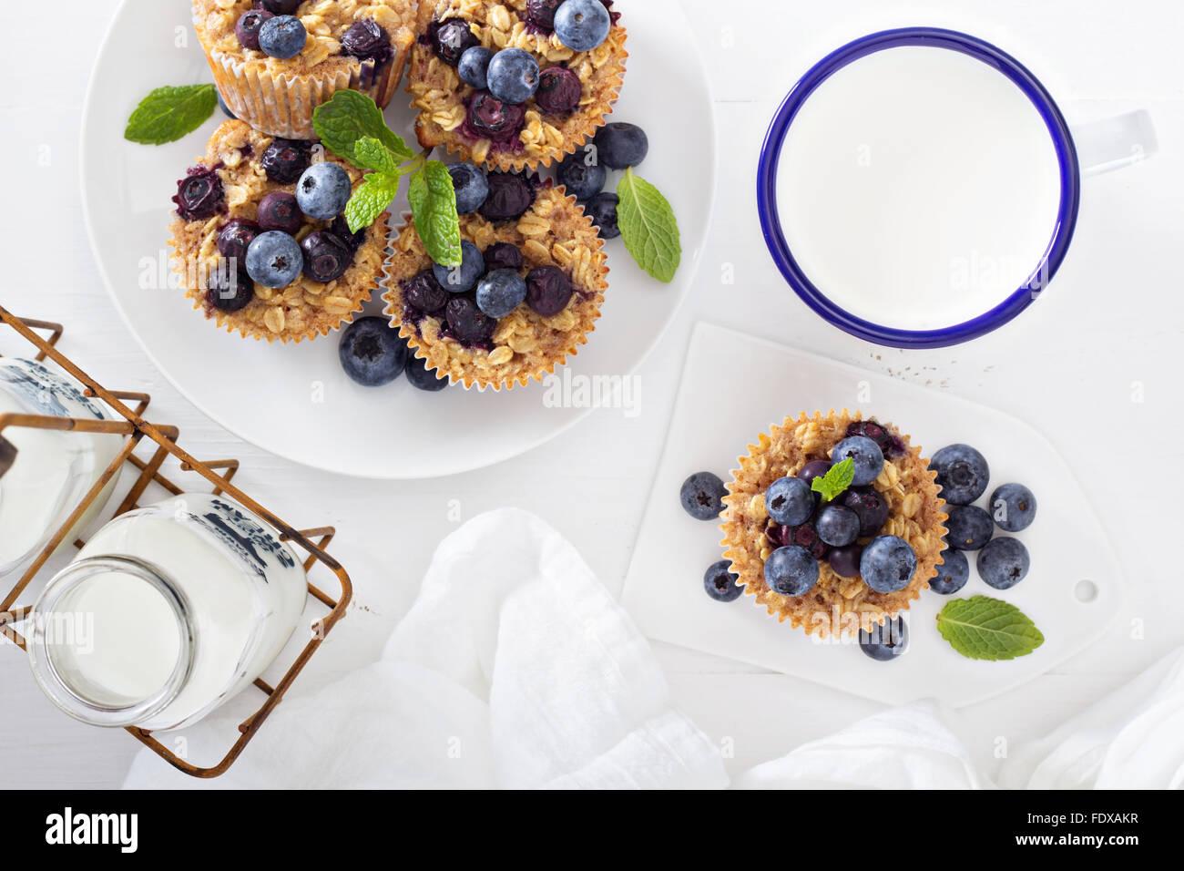 Cotto al forno muffin ai fiocchi d'avena con mirtilli servite con latte Immagini Stock