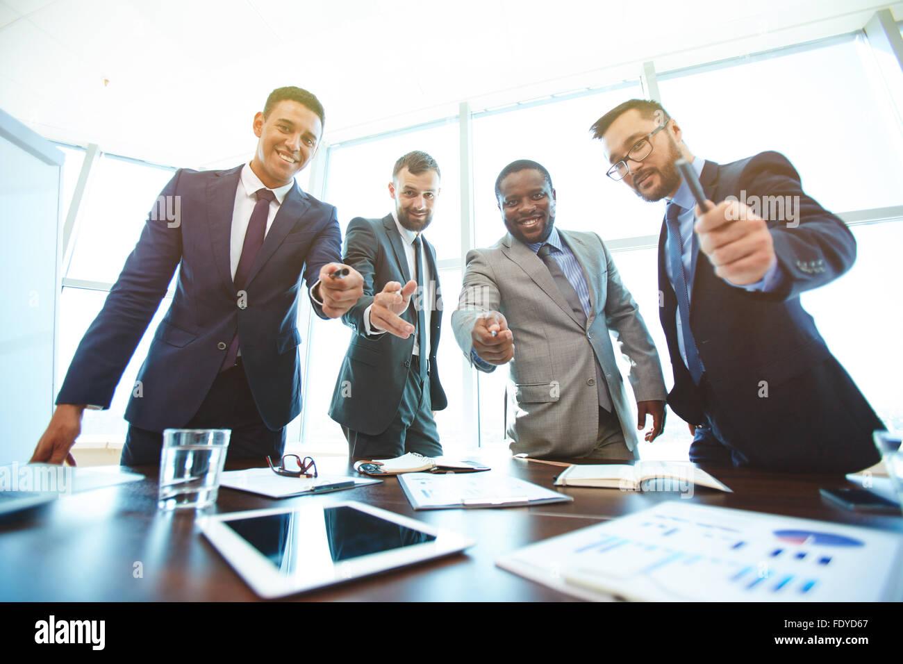 Eleganti uomini d'affari offrendo penne a firmare il contratto Immagini Stock