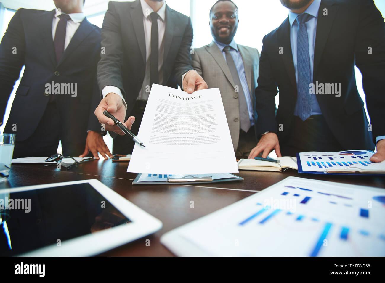 Gruppo di dipendenti offrendo al cliente di firmare contratto di business Immagini Stock