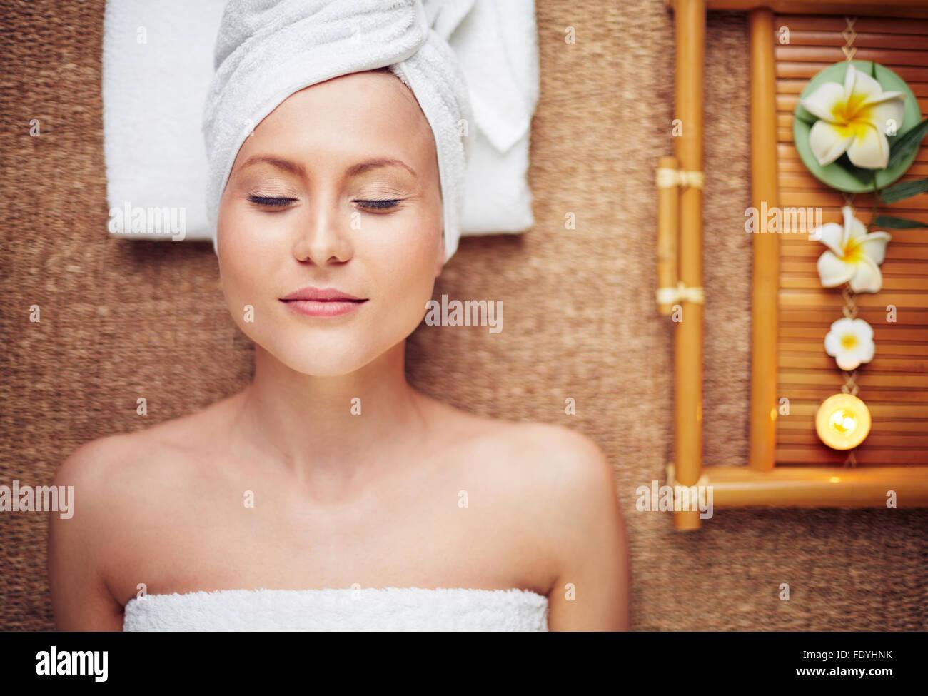 Giovane donna con gli occhi chiusi rilassarsi nel salone di bellezza Immagini Stock
