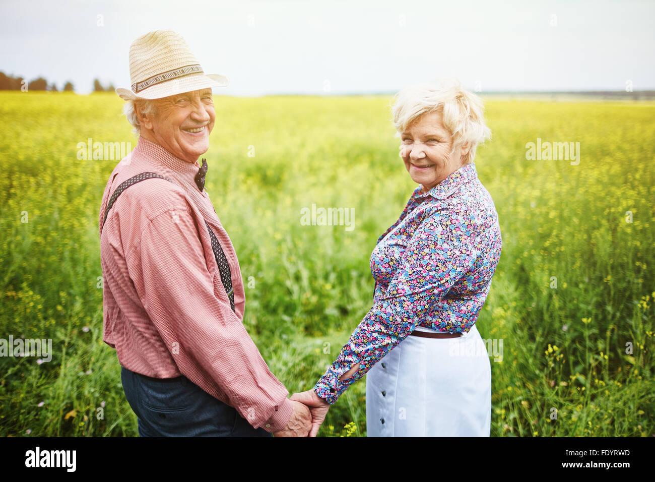 Seniors affettuoso tenendo premuto dalle mani mentre in piedi in Prato Foto Stock