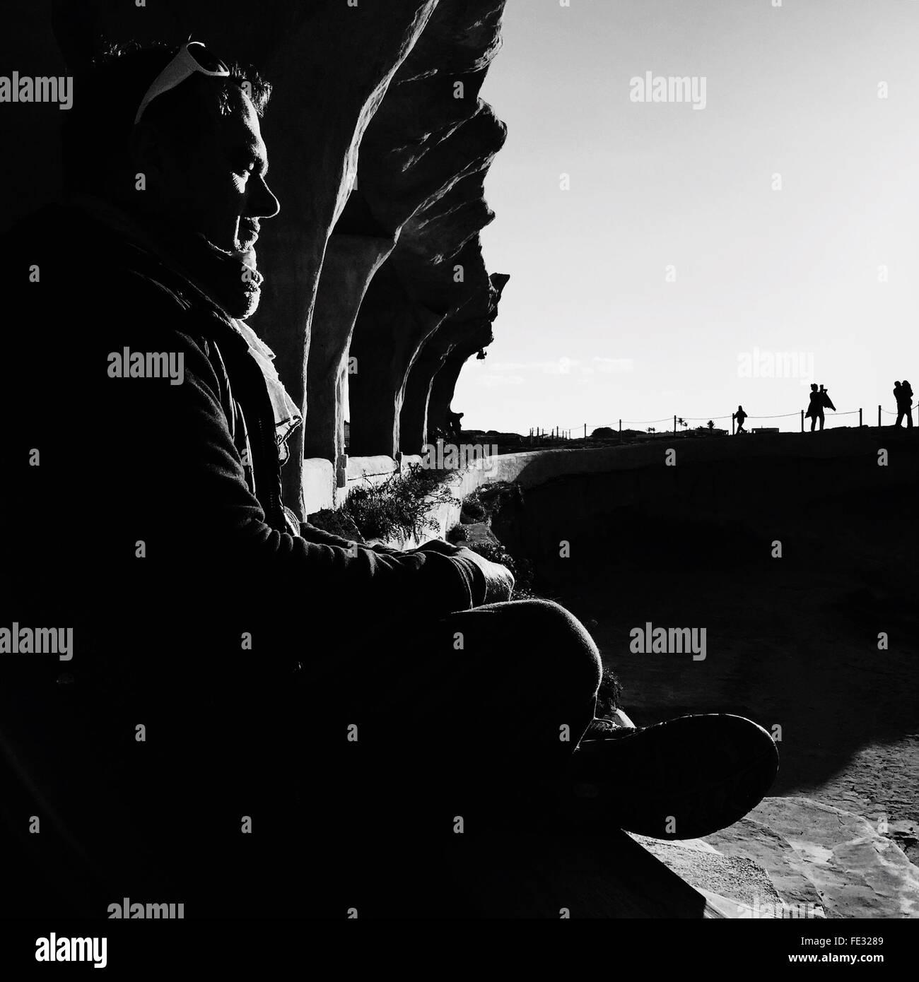 Vista laterale dell'uomo la meditazione sulla Cala Comte Beach sulla giornata di sole Immagini Stock