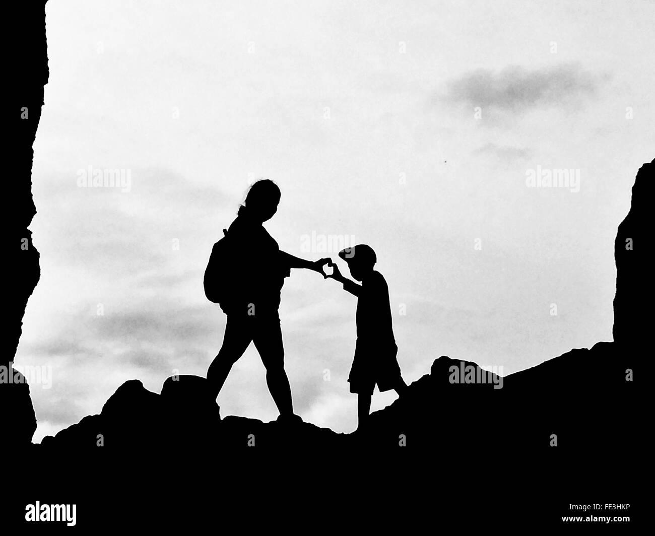 Basso angolo vista di Silhouette madre e figlio messa a forma di cuore con la mano Immagini Stock