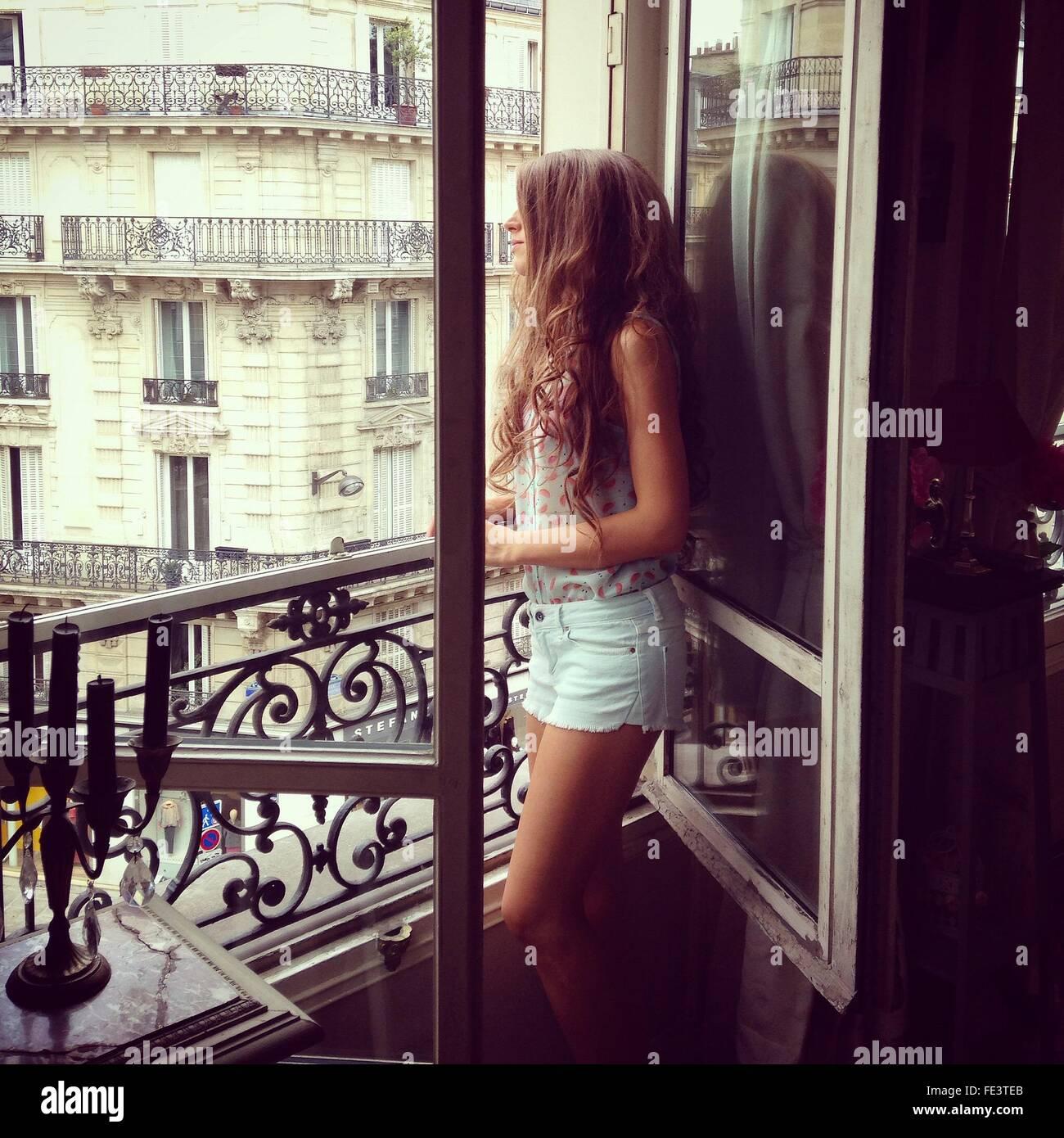 Vista laterale della giovane donna guardando attraverso la finestra Immagini Stock