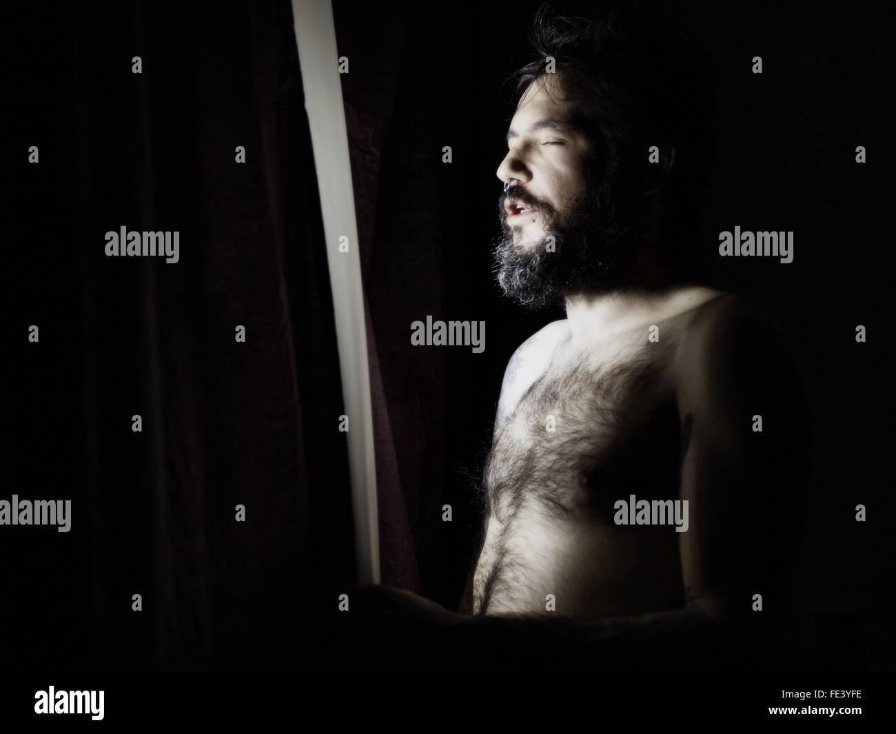 Uomo in piedi alla finestra con gli occhi chiusi Immagini Stock