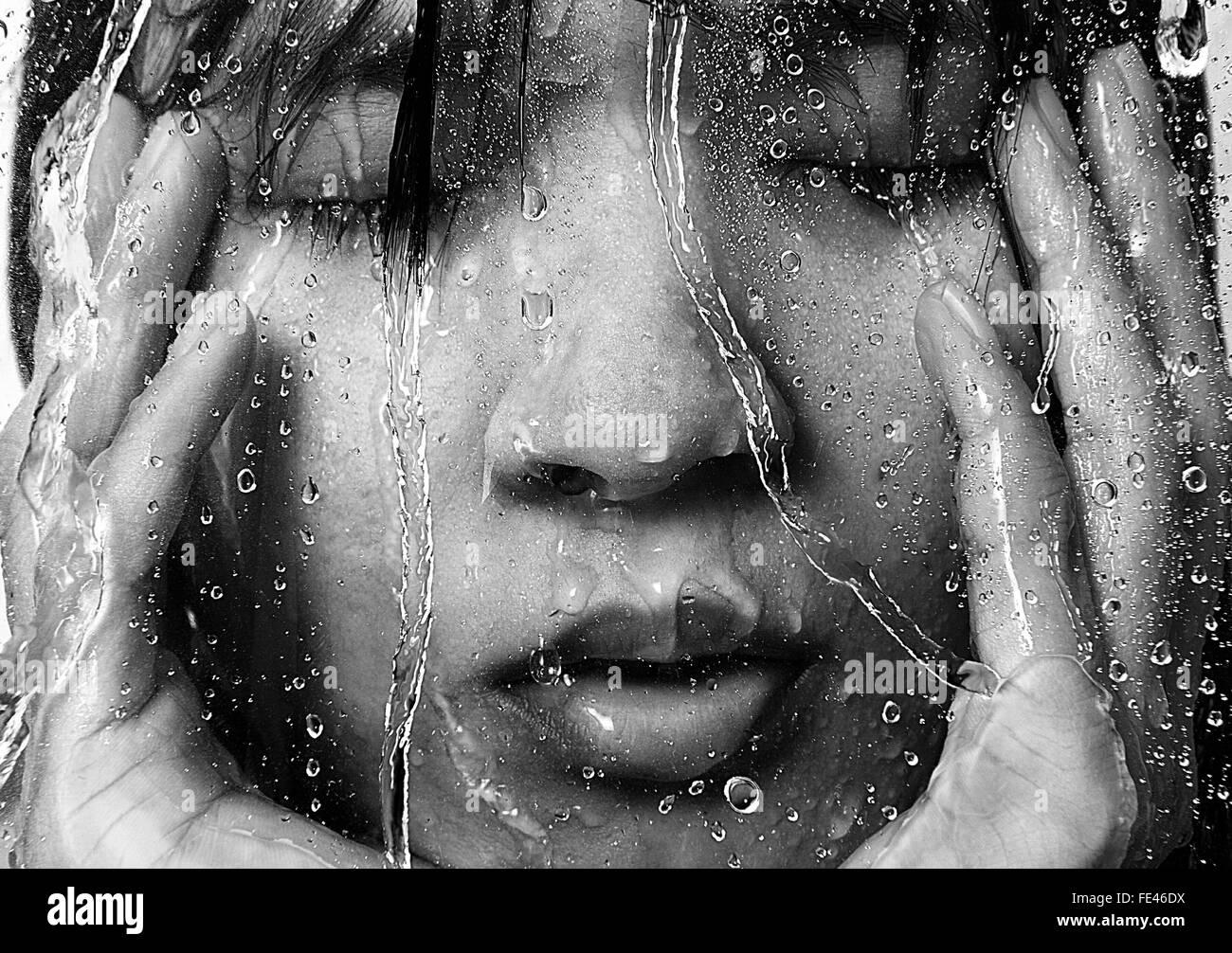 Donna in doccia visto attraverso il vetro bagnato Immagini Stock