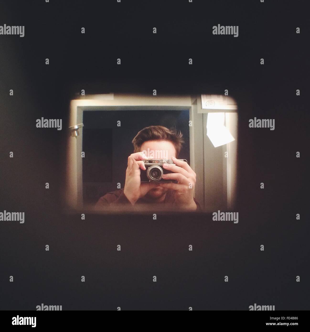 La riflessione di uomo in specchio mentre si fotografa Immagini Stock