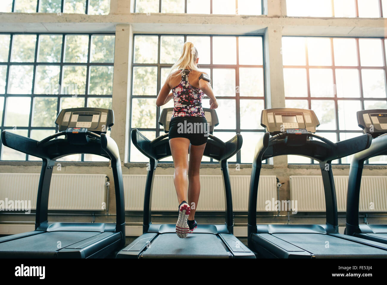 Inquadratura orizzontale di donna jogging sul tapis roulant al club della salute. Lavoro femminile in una palestra Immagini Stock