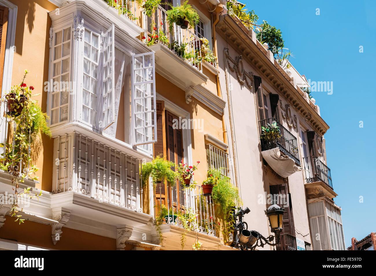 L'architettura dei vecchi edifici con grandi finestre e balconi montati su strette strade di Malaga, in Spagna. Immagini Stock