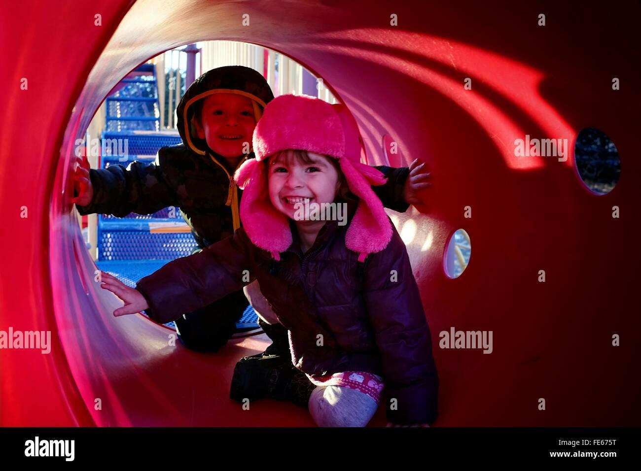 I bambini nel parco giochi Tunnel Immagini Stock