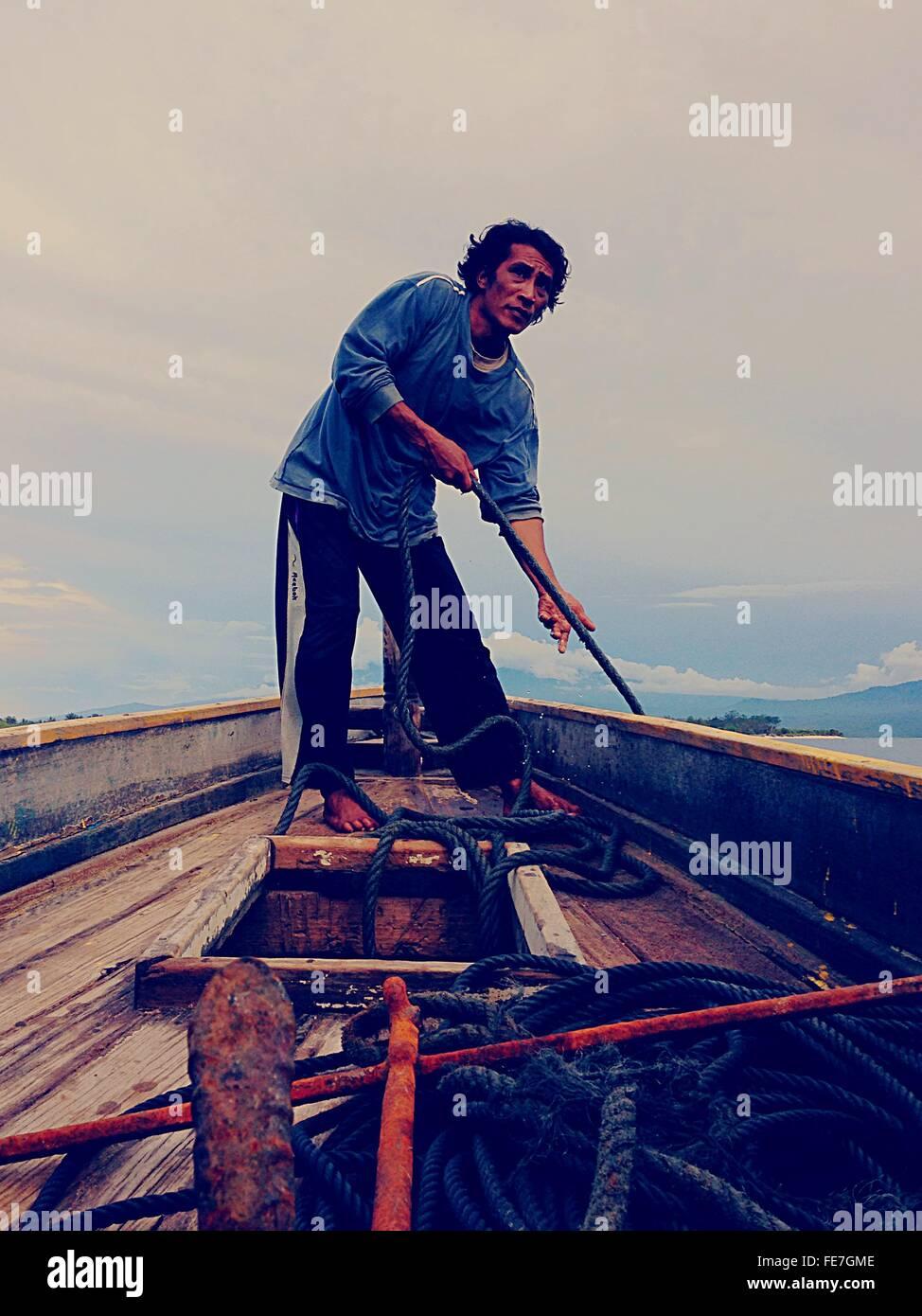 Lunghezza completa dell'uomo tirando la corda in barca contro Sky Immagini Stock