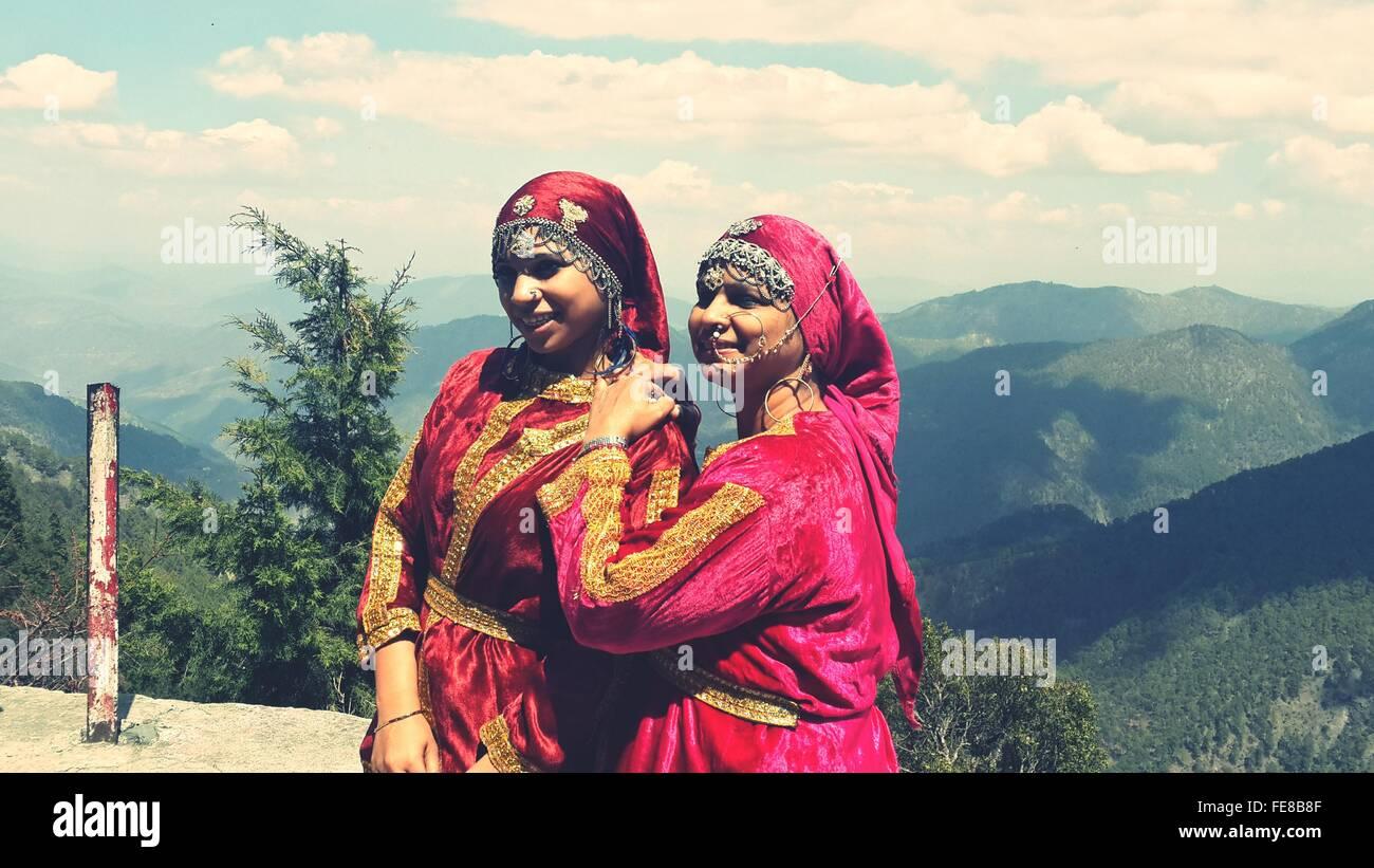 Madre e figlia in Abbigliamento tradizionale contro la montagna Immagini Stock