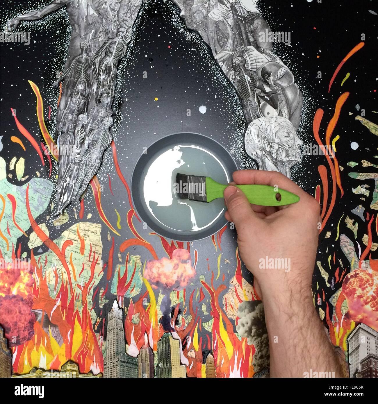 Uomo con la pittura con il pennello di colore grigio sulla pittura Immagini Stock