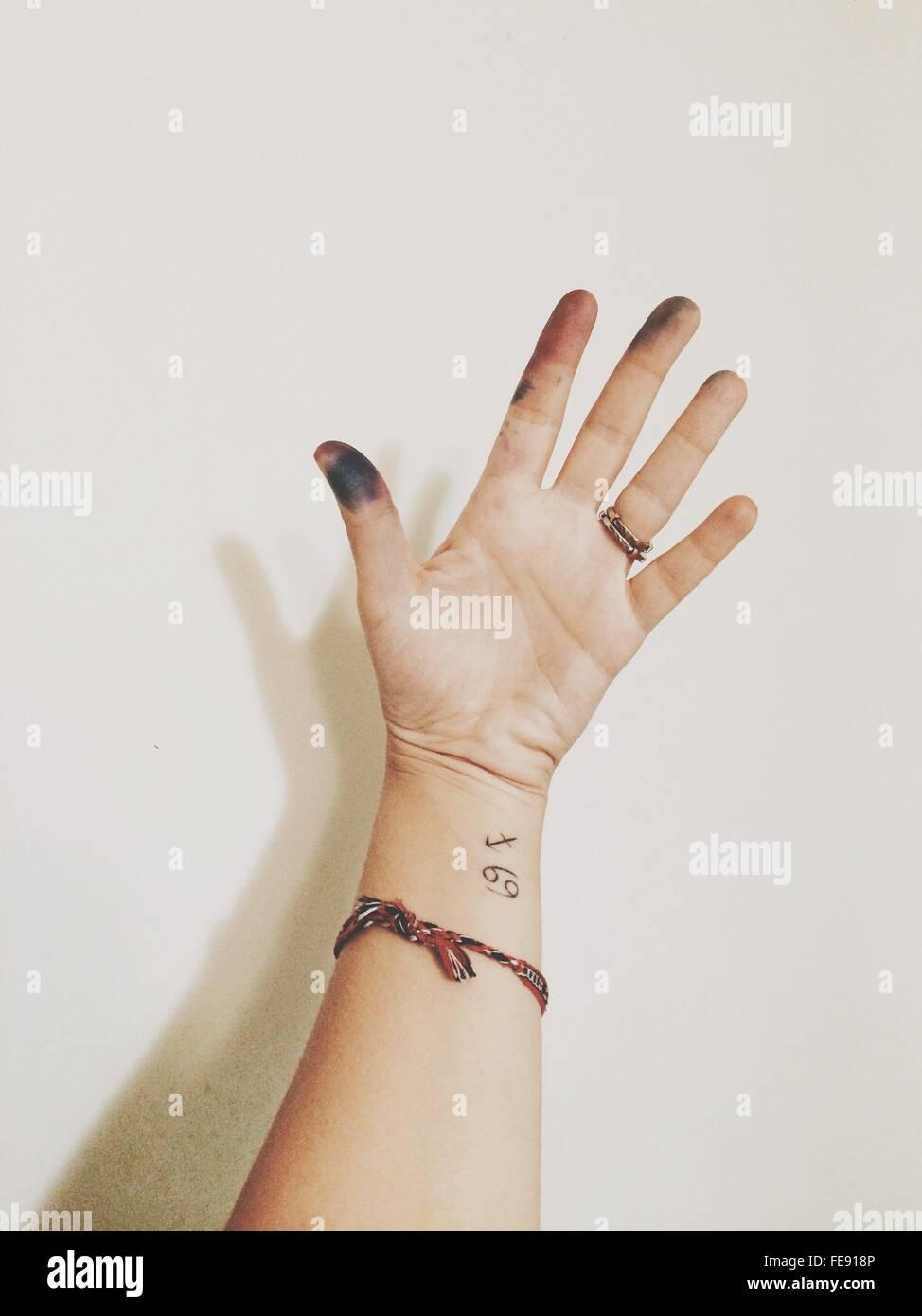 Mano di donna, con Tattoo e le dita sporche Immagini Stock