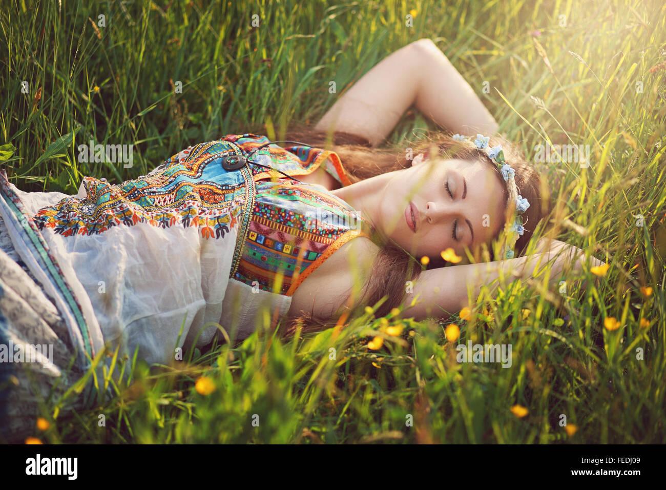 Bella donna hippie pacificamente dormire in prato primavera Immagini Stock