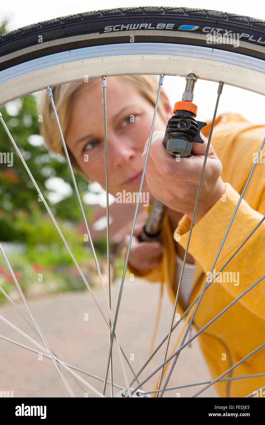 Pompe donna i pneumatici per la sua ruota di bicicletta Immagini Stock