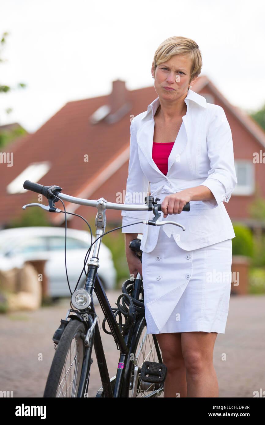 Donna con costume business ha un pneumatico sgonfio e spingendo la sua bicicletta Immagini Stock